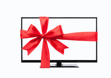 Wide screen tv monitor tied with red ribbon. Isolated on white Royalty Free Stock Images
