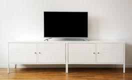 Wide screen TV on white stand near light wall Stock Images