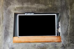 Wide screen TV on wooden commode near grey wall. stock photo