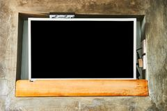 Wide screen TV on wooden commode near grey wall. Black screen TV stock photo