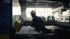 Wide sheets of metal are braided in big rolls at plant, time lapse. Two workers of the plant or factory lift sheet metal. Cling and crane hooks are on the stock footage