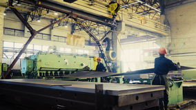 Wide sheets of metal are braided in big rolls at plant, time lapse. Two workers of the plant or factory lift sheet metal. Cling and crane hooks are on the stock video footage