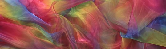 Beautiful Cascading Rainbow Chiffon Banner Background. Wide shimmering rainbow colored chiffon material cascading in gentle folds Royalty Free Stock Images