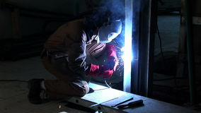 Wide shoot of craftsman welding close to the floor