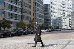 Wide shot of African American business man walking in the busine. Young African American business man walking across the street, photographed in NYC in September Royalty Free Stock Images