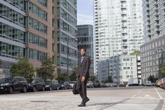 Wide shot of African American business man walking in the busine. Young African American business man walking across the street, photographed in NYC in September Royalty Free Stock Photo