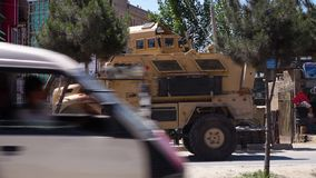 A parked armored car in Kabul. A wide shot of an armored truck parked in the city of Kabul stock video footage