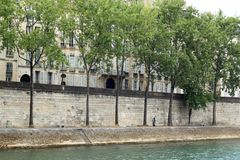 Wide shot of a beautiful canal and a stone fence with trees with a loving couple kissing each other stock images