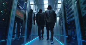 Two hackers walking through rows of servers. Wide shot from behind of a two hackers walking through corporate data center with rows of working rack servers stock video footage