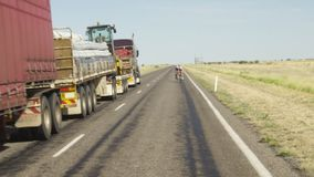 Cyclists on road with truck in slow motion. A wide shot of bikers on road with truck on road in slow motion stock video