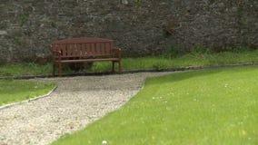 A brown bench on a tidy gravel sidewalk