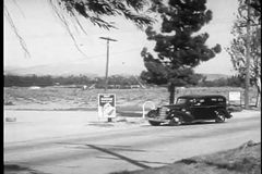 Wide shot of car pulling into service station, 1930s stock footage