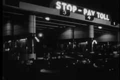 Wide shot of cars going through toll booth at night, 1950s stock video footage