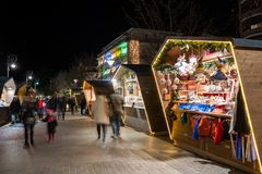 Wide shot of a Christmas market booth in Merano south tyrol italy, with a beautiful light during night and people bassing by on stock image