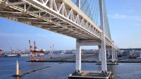 Wide shot of cruise passing under Japan yokohama bridge stock footage