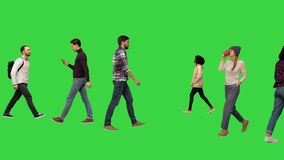 Different casual people walking by on a green screen, chroma key.