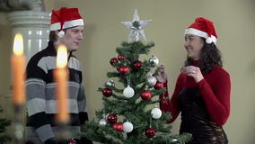 Wide shot of girl decorating Christmas tree with shiny star. Young romantic couple decorating Christmas tree by a fireplace with red and silver ornaments, red stock video