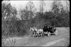 Wide shot of horse drawn carriage traveling through countryside