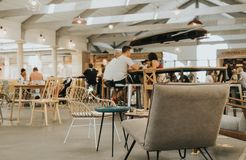 Wide shot of a large cafe with people sitting around tables at daytime