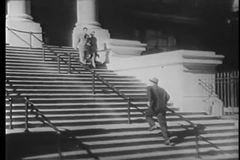 Wide shot of man running up stairs into building stock footage