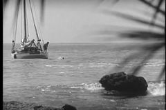 Wide shot of men on boat diving into the ocean stock video footage