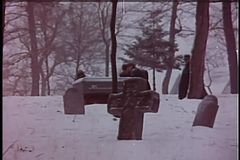 Wide shot of men carrying coffin through cemetery in winter