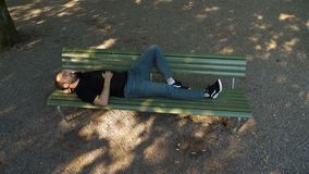 Men take a nap on a bench in the park. Wide shot.Men take a nap on a bench in the park. Professional shot in 4K resolution. 02. You can use it e.g. in your stock video