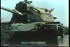 Wide shot of military tanks traveling over grassy area stock video footage