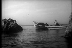 Wide shot of people in motorboat with row boat attached