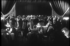 Wide shot of people sitting and dancing in nightclub stock footage