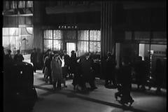 Wide shot of people walking along city street stock video footage