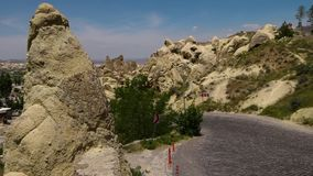 A pointy rock next to a road with road signs. Wide shot of a pointy rock next to a windy hilly road with road signs and two cars leading to a settlement stock video