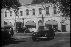 Wide shot of police car chase on San Fernando street, 1940s