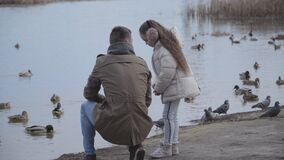 Wide shot portrait of pretty brunette girl talking with young father on riverbank. Caucasian child spending free time