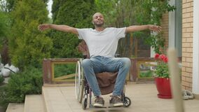 Wide shot portrait of smiling cheerful paraplegic man in wheelchair with stretched hands on sunny day outdoors. Happy