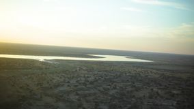 River and grayish land. A wide shot of a river and grayish land with sunset hitting the lens of the camera stock video footage