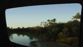River and trees with sky shot. A wide shot of a river and trees while camera slowly moves to the right while remaining focus on the river stock footage