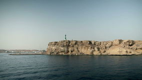 Wide shot of rocky cliffs with lighthouse at tourist resort in Egypt. Tourist resort in Egypt, traveling on the sea, sightseeing animals and sunken ships stock video footage