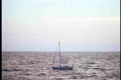 Wide shot of a sailboat drifting on an open ocean