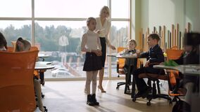 Wide shot of schoolgirl declaiming in classroom with teacher and classmates listening. Portrait of confident Caucasian