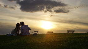 Wide shot of silhouette couple sharing a sunset kiss Stock Photo