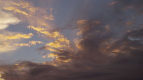 Yellowish sky and clouds. A wide shot of the sky on sunset. Panning shot to the right stock video footage