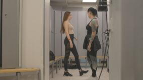 Wide shot of sportive athletic women talking in gym locker room after training. Portrait of confident Caucasian