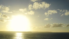 Wide shot of a sunset in timelapse over the ocean and cliffs on the horizon. Zooming progressively on the cliffs.