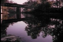 Wide shot of trees and covered bridge reflecting in river stock video
