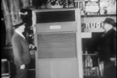 Wide shot of two men checking out old fashioned air conditioner stock video footage