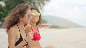 Wide Shot Two women sunbathing on beach. In sunglasses stock footage