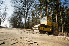 Wide shot of the vintage road roller. At road in the forest royalty free stock photography