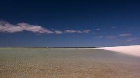 White sand beach and a blue sky. A wide shot of a white sand and a blue sky. Camera pans to the left stock video
