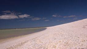 White sand beach and a blue sky. A wide shot of a white sand and a blue sky. Camera pans to the left stock video footage